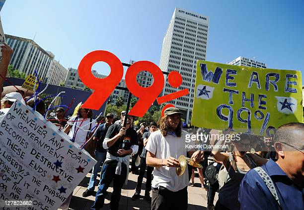 "Protesters hold signs as they march to Los Angeles City Hall during the ""Occupy Los Angeles"" demonstration in solidarity with the ongoing ""Occupy..."