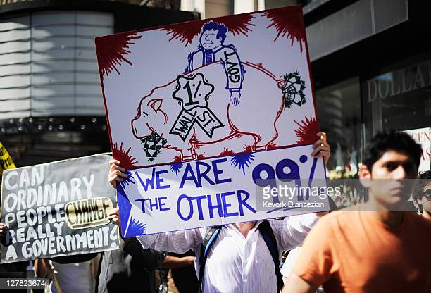 """Protesters hold signs as they march to Los Angeles City Hall during the """"Occupy Los Angeles"""" demonstration in solidarity with the ongoing """"Occupy..."""