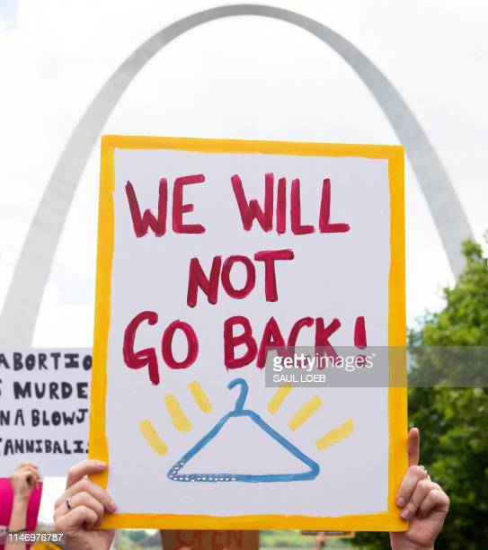 Protesters hold signs as they rally in support of Planned Parenthood and pro-choice and to protest a state decision that would effectively halt...