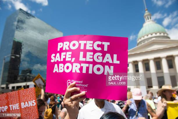 Protesters hold signs as they rally in support of Planned Parenthood and prochoice and to protest a state decision that would effectively halt...