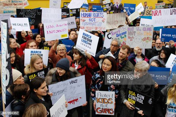 Protesters hold signs as they rally outside the US Embassy in London on March 24, 2017 in solidarity with the March For Our Lives rally against gun...