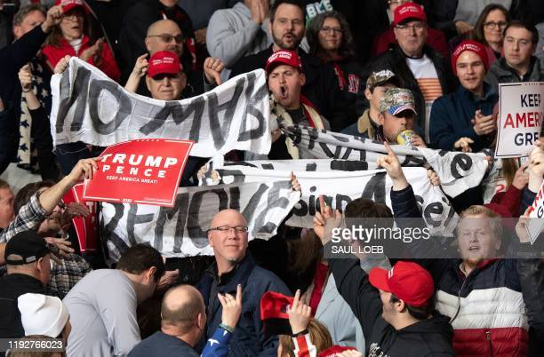"""Protesters hold signs as US President Donald Trump holds a """"Keep America Great"""" campaign rally at Huntington Center in Toledo, Ohio, on January 9,..."""