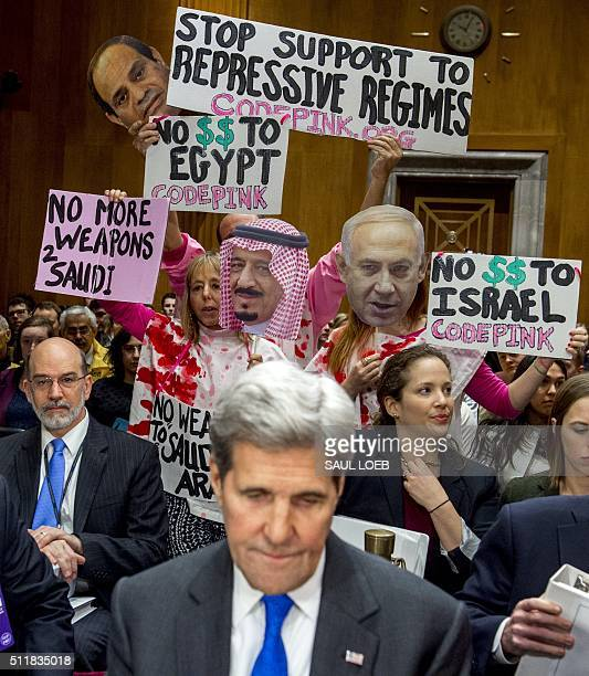 Protesters hold signs as US Secretary of State John Kerry arrives to testify during a Senate Foreign Relations Committee hearing about the budget on...