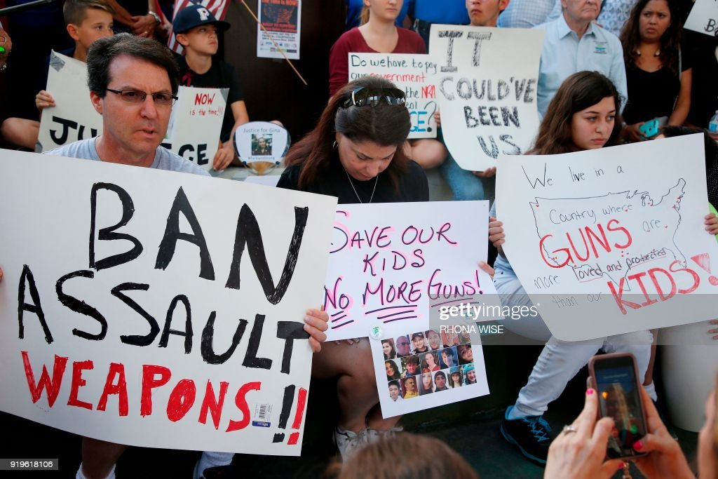 Protesters hold signs at a rally for gun control at the Broward County Federal Courthouse in Fort Lauderdale, Florida on February 17, 2018. Seventeen perished and more than a dozen were wounded in the hail of bullets at Marjory Stoneman Douglas High School in Parkland,Florida the latest mass shooting to devastate a small US community and renew calls for gun control. /