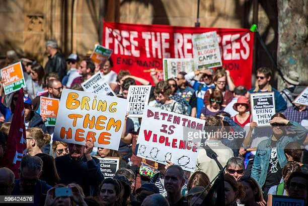 Protesters hold signs at a rally to demand all asylum seekers and refugees be brought to Australia following PNG government's decision to close the...