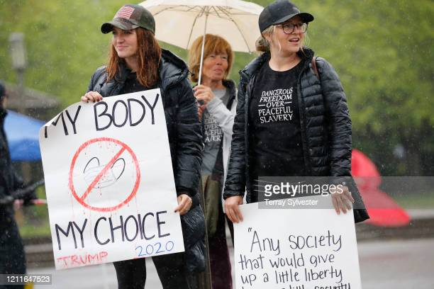 Protesters hold signs at the ReOpen Oregon Rally on May 2 2020 in Salem Oregon Demonstrators gathered at the state capitol to demand a reopening of...