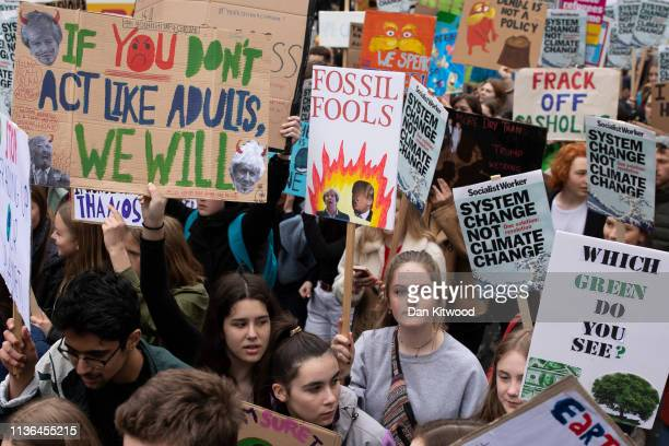 Protesters hold signs at the YouthStrike4Climate student march on April 12 2019 in London United Kingdom Students are protesting across the UK due to...