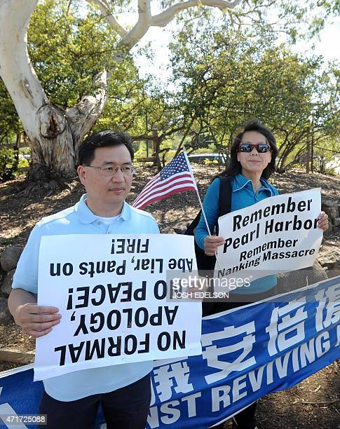 Protesters hold signs before the arrival of Japanese Prime Minister Shinzo Abe at Tesla headquarters in Palo Alto California on April 30 2015 Shinzo...