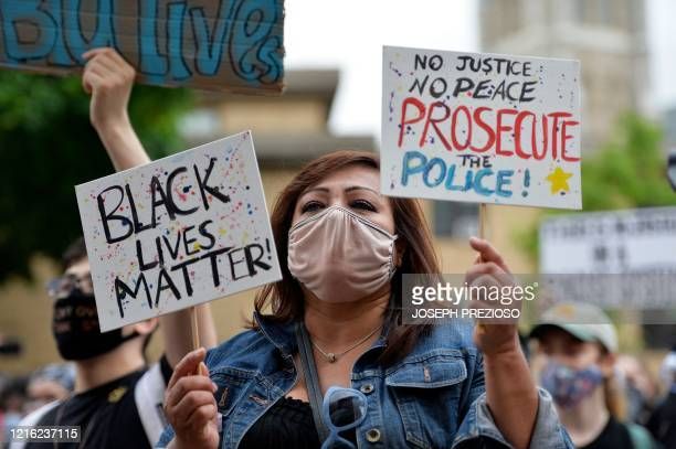 Protesters hold signs during a Black Lives Matter protest against police brutality and racism in the US, including the recent deaths of George Floyd,...