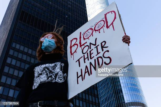 Protesters hold signs during a demonstration at Trump Tower following the killing of George Floyd by Minneapolis Police on May 30, 2020 in Chicago,...