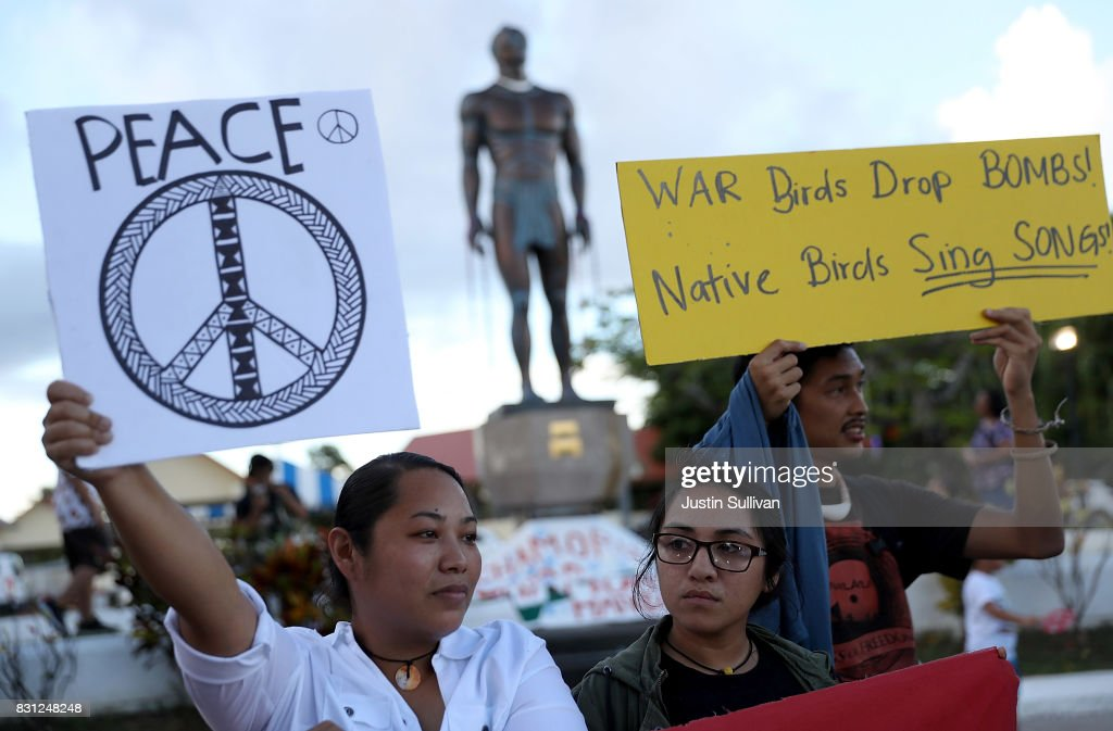Protesters hold signs during a People for Peace Rally at the Chief Quipuha Statue on August 14, 2017 in Hagatna, Guam. The American territory of Guam remains on high alert as a showdown between the U.S. and North Korea continues. North Korea has said that it is planning to launch four missiles near Guam by the middle of August. Guam is home to around 7,000 American troops and 160,000 residents.