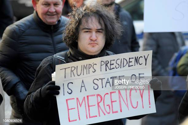 Protesters hold signs during a protest rally by government workers and concerned citizens against the government shutdown on Friday January 11 2019...