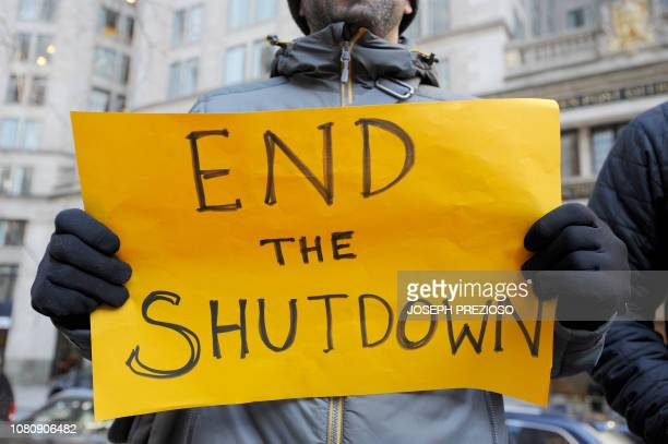 Protesters hold signs during a rally and protest by government workers and concerned citizens against the government shutdown on Friday January 11...