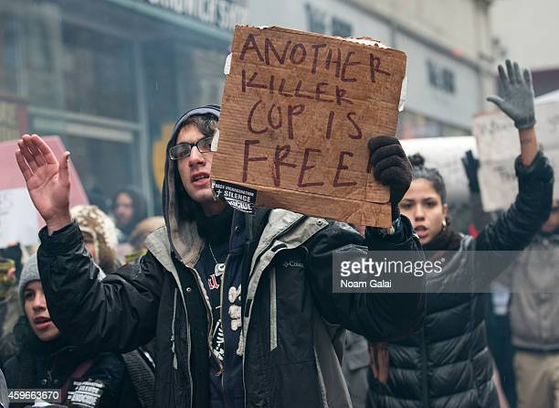 Protesters hold signs during the 88th Annual Macys Thanksgiving Day Parade on November 27, 2014 on the streets of New York City.