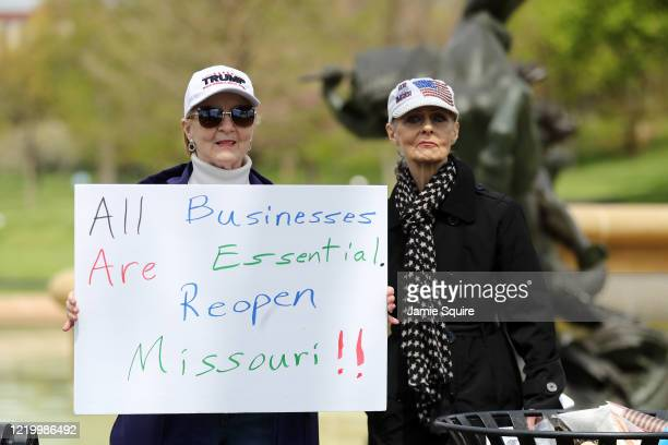 Protesters hold signs encouraging people to demand that businesses be allowed to open up, and people be allowed to work at the Country Club Plaza on...