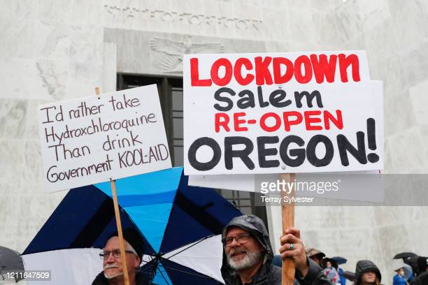 Protesters hold signs in front of the state capitol at the ReOpen Oregon Rally on May 2 2020 in Salem Oregon Demonstrators gathered at the state...