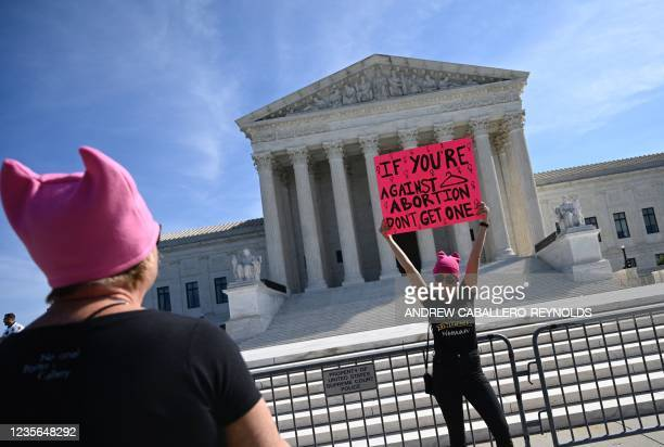 Protesters hold signs in front of the Supreme Court during the Women's March and Rally for Abortion Justice in Washington, DC, on October 2, 2021. -...
