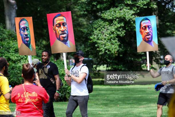Protesters hold signs of George Floyd during the Commitment March at the Lincoln Memorial on August 28, 2020 in Washington, DC. Rev. Al Sharpton and...