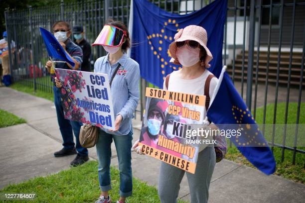 Protesters hold signs outside of the Chinese consulate in Houston on July 24 after the US State Department ordered China to close the consulate. -...