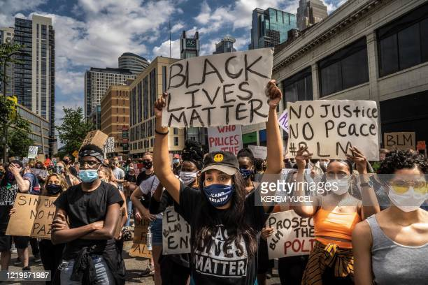 TOPSHOT Protesters hold signs outside the Minneapolis 1st Police precinct during a demonstration against police brutality and racism on June 13 2020...