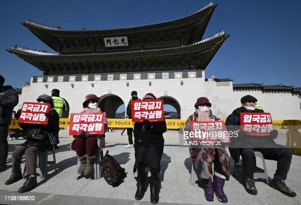 Protesters hold signs reading Ban entry immediately during a protest calling on the South Korean government to enforce an entry ban on Chinese...