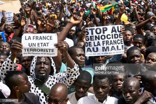 TOPSHOT Protesters hold signs reading France a terrorist state and Stop France's genocide in Mali during a demonstration called by the president of...