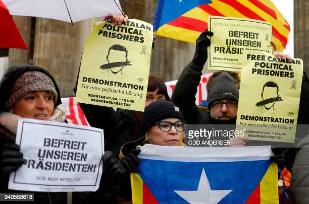 Protesters hold signs reading Liberate our President and hold the Estelada Catalan flag while taking part in a demonstration organized by the...