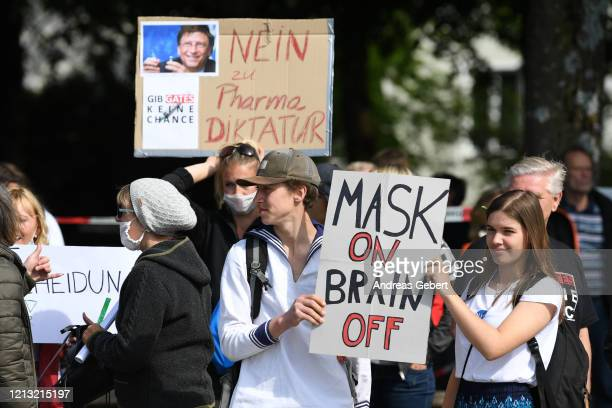 Protesters hold signs reading Mask on, brain off and I am not a conspirator, I am just a mother and Give Gates no chance during a protest of about...