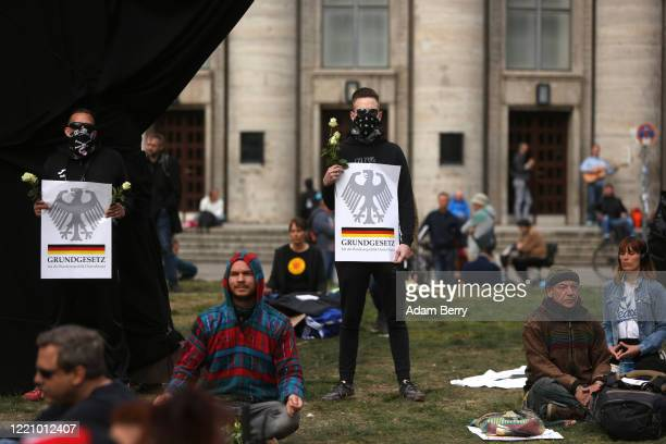 Protesters hold signs referring to the Grundgesetz, or German constitution known as the basic law, as they demonstrate against restrictions on public...