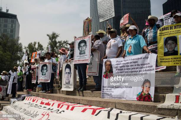Protesters hold signs with images of their missing relatives during a march on Mother's Day on May 10 2017 in Mexico City Mexico Mothers whose...