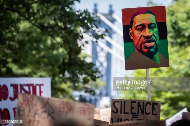 Protesters hold signs with painted portraits of George Floyd with the PanAfrican colors of Red Black and Green behind them with the Manhattan Bridge...