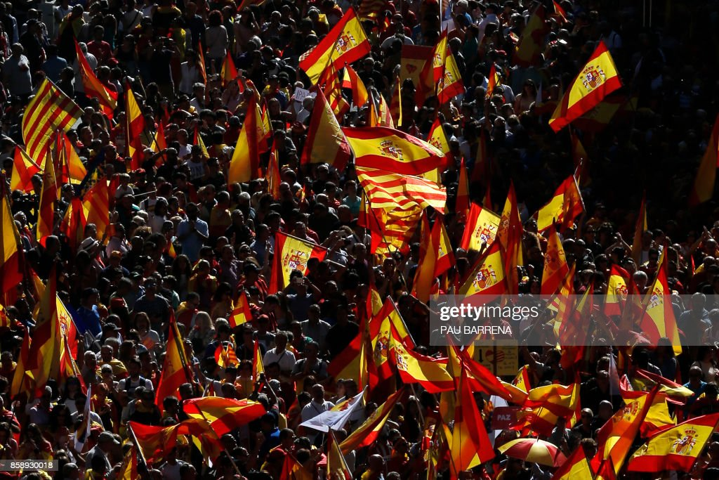 Protesters hold Spanish and Catalan flags during a demonstration called by 'Societat Civil Catalana' (Catalan Civil Society) to support the unity of Spain on October 8, 2017 in Barcelona. Spain braced for more protests despite tentative signs that the sides may be seeking to defuse the crisis after Madrid offered a first apology to Catalans injured by police during their outlawed independence vote. /