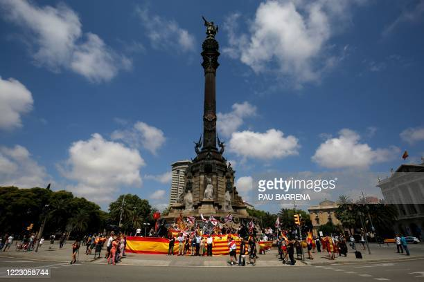 Protesters hold Spanish and Catalan Senyera flags along with Cross of Burgundy flags during a demonstration organised by Spain's far-right Vox party...