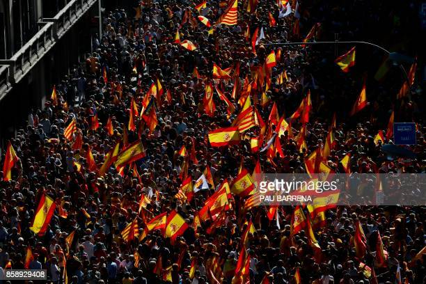 TOPSHOT Protesters hold Spanish flags during a demonstration called by 'Societat Civil Catalana' to support the unity of Spain on October 8 2017 in...