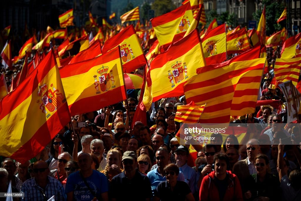 TOPSHOT - Protesters hold Spanish flags during a demonstration called by 'Societat Civil Catalana' (Catalan Civil Society) to support the unity of Spain on October 8, 2017 in Barcelona. Ten of thousands of flag-waving demonstrators packed central Barcelona to rally against plans by separatist leaders to declare Catalonia independent following a banned secession referendum. Catalans calling themselves a 'silent majority' opposed to leaving Spain broke their silence after a week of mounting anxiety over the country's worst political crisis in a generation. GUERRERO