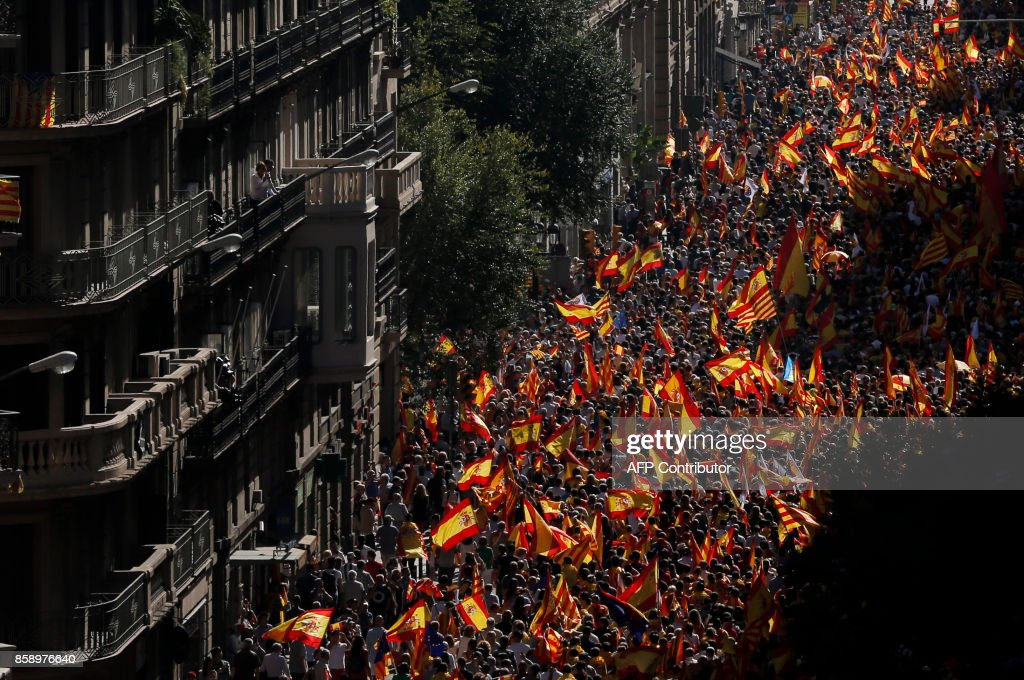 TOPSHOT - Protesters hold Spanish flags during a demonstration called by 'Societat Civil Catalana' (Catalan Civil Society) to support the unity of Spain on October 8, 2017 in Barcelona. Ten of thousands of flag-waving demonstrators packed central Barcelona to rally against plans by separatist leaders to declare Catalonia independent following a banned secession referendum. Catalans calling themselves a 'silent majority' opposed to leaving Spain broke their silence after a week of mounting anxiety over the country's worst political crisis in a generation. BARRENA
