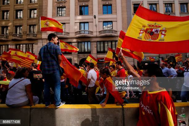 """Protesters hold Spanish flags during a demonstration called by """"Societat Civil Catalana"""" to support the unity of Spain on October 8, 2017 in..."""