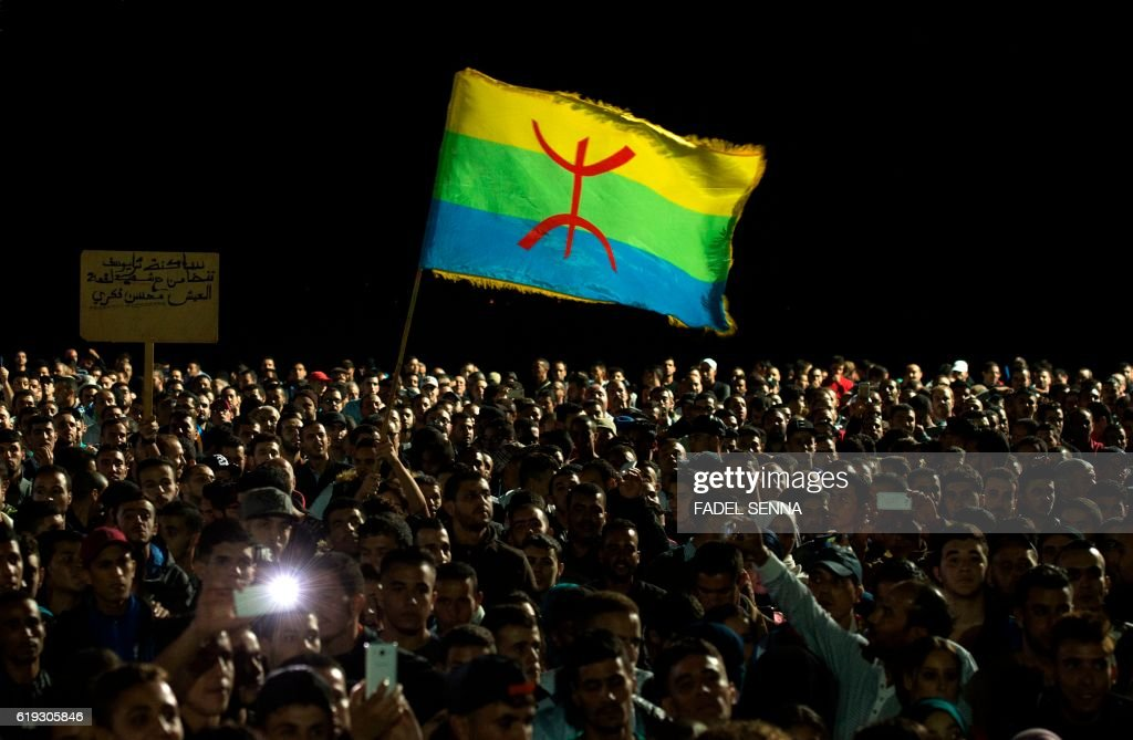 Protesters hold the Amazigh flag as they shout slogans in