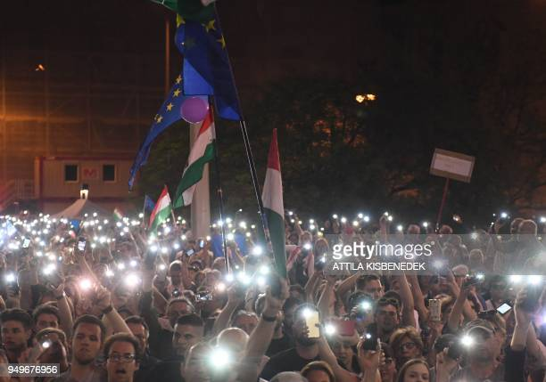 Protesters hold the European and the Hungarian flag while taking part in an antigovernment demonstration in Budapest Hungary on April 21 2018 Tens of...