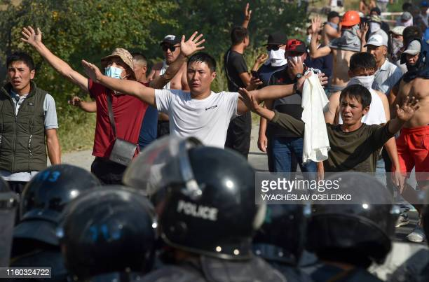Protesters hold their arms up in front of members of the Kyrgyz special forces during clashes between supporters of Kyrgyzstan's former president and...