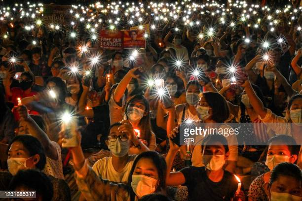 Protesters hold their mobile phones during a candlelight vigil to honour those who have died during demonstrations against the military coup in...