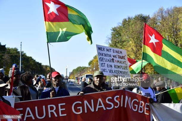 Protesters hold Togolese flags and placards during a demonstration outside the AXICA Congress center where a G20 Investment Summit takes place as...