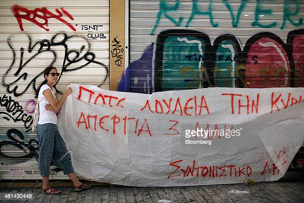 Protesters hold up a large banner in front of a store in order to demonstrate against stores opening and trading on Sundays in Athens Greece on...
