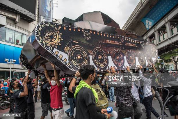 Protesters hold up a mock-up tank during the car mob rally. Anti-government protesters gathered at Asok intersection before they drove their vehicles...