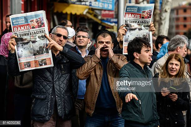 Protesters hold up a new newspaper by the former team of Zaman called 'Yarina Bakis' during a demonstration near the headquarters of the newspaper...