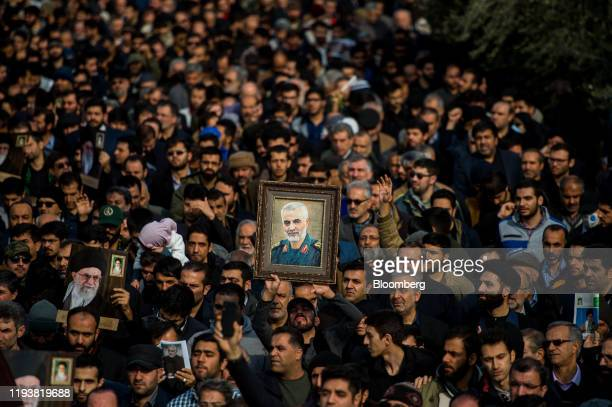 Protesters hold up an image of Qassem Soleimani, an Iranian commander, during a demonstration following the U.S. Airstrike in Iraq which killed him,...