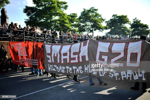 Protesters hold up banners one saying 'Smash G20' as they take part in the Welcome to Hell protest march on July 6 2017 in Hamburg Germany Leaders of...