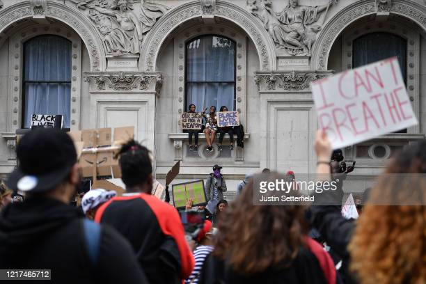 Protesters hold up 'Black Lives Matter' signs as they sit on a windowsill of the Foreign and Commonwealth Office during the Black Lives Matter...