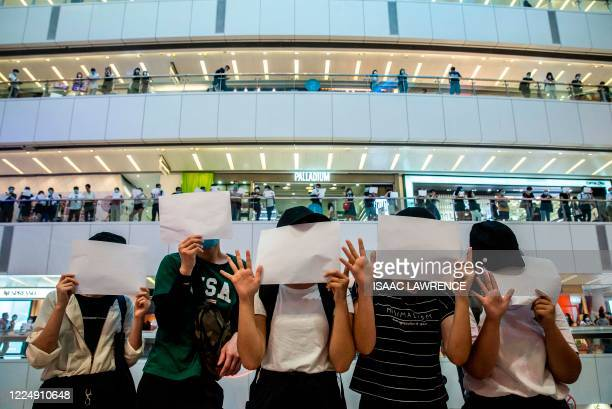 Protesters hold up blank papers during a demonstration in a mall in Hong Kong on July 6 in response to a new national security law introduced in the...