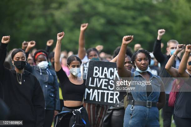 Protesters hold up fists at a gathering in support of the Black Lives Matter movement on Woodhouse Moor in Leeds in northern England on June 21 in...